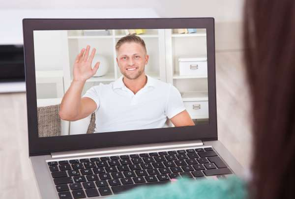 Young woman video conferencing with friend on laptop from home
